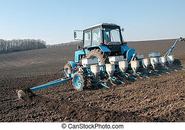 Tractor with sower on the field - Blue tractor with sower on...