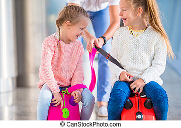 Adorable little girls having fun in airport sitting on...