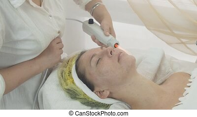 Cosmetologist use darsonval on woman face in beauty saloon....