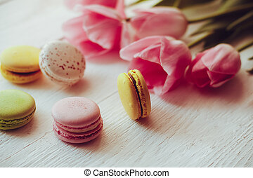 A beautiful bouquet of pink tulips with colorful macaroons...