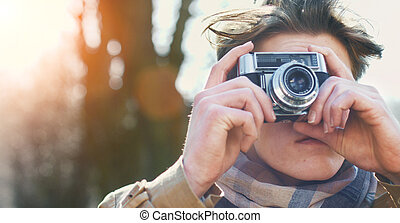 Attractive Tourist taking a photograph with vintage camera