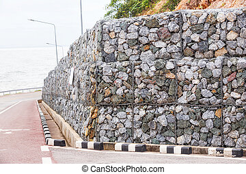 Stone wall with wire mesh for falling rock protection from...
