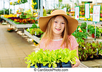 Kid girl buying vegetable seedlings in garden center