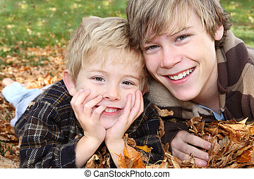 Brother\'s laying  in a pile of leaves