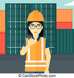 Stevedore standing on cargo containers background - An asian...