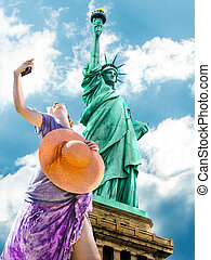 Woman photographing the Statue of Liberty
