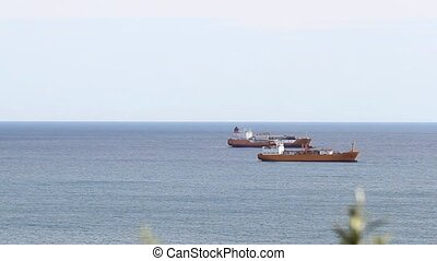 Freight ships anchored in the open sea Blue calm ocean under...