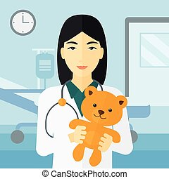 Pediatrician holding teddy bear. - An asian pediatrician...