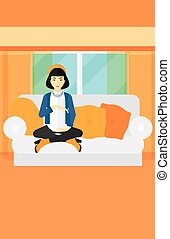 Pregnant woman sitting on sofa - An asian pregnant woman...