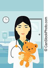 Pediatrician holding teddy bear - An asian pediatrician...