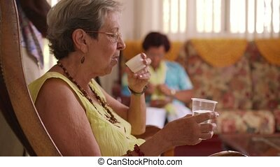 Old Woman In Hospice Taking Medicine Pill And Water