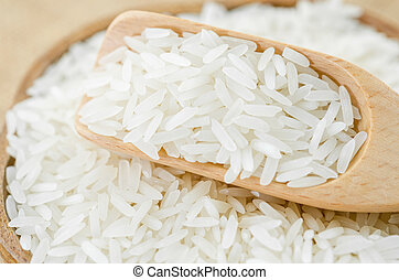 Jasmine rice with wooden spoon on wooden cup