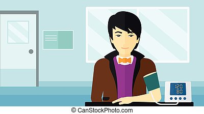 Blood pressure measurement - An asian man with blood...