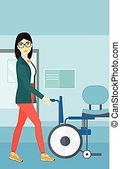 Woman pushing wheelchair - An asian woman pushing empty...