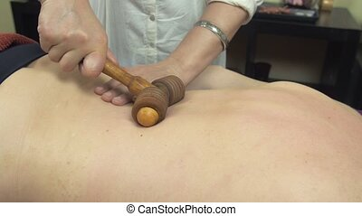 Masseuse make therapeutic massage of backbone by wooden...
