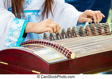 Girl playing classical Chinese instruments - A girl is...