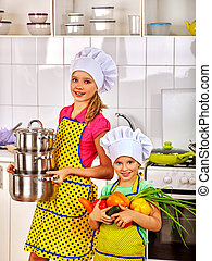 Child cooking at kitchen. - Child in cooking hat holding...