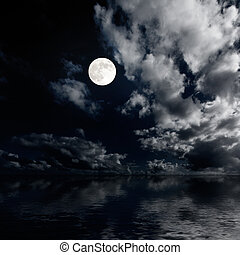 Moon and clouds above sea at night photo
