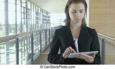Slow motion businesswoman walking in office building working on tablet pc ipad