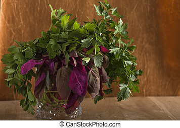 Bunch of red orach with parsley and lovage in glass over old...