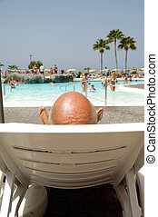 Bald headed man on vacation - Bald headed man relaxing by...