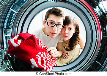 Funny couple loading clothes to washing machine