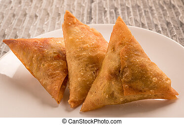 Samosas a spicy blend of vegetables or meat wrapped in a...