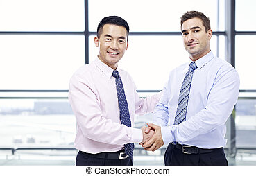 businessmen shaking hands at airport - two businessmen, one...