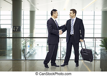 business people shaking hands at airport - two businessmen,...