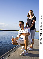 Mid-adult couple on dock by water enjoying drink