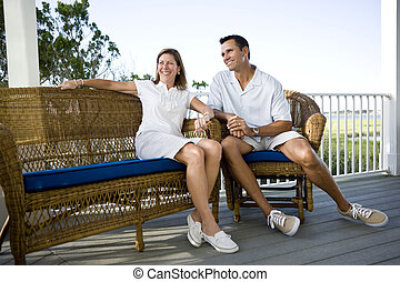 Happy mid-adult couple sitting together on terrace