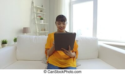happy young asian woman with tablet pc at home - people,...