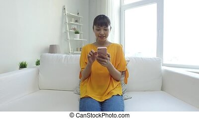 happy asian woman with smartphone at home - people,...