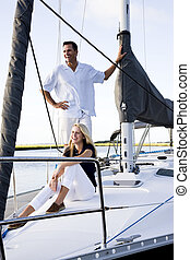 Father and teenage daughter on sailboat at dock