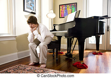 Teenage boy sitting on piano bench looking down - Serious...
