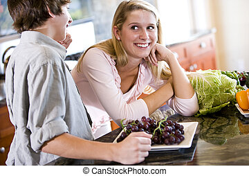 Teenage girl leaning on kitchen counter with brother