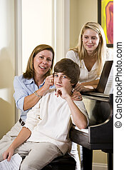 Family sitting on piano bench, mother teasing son - Family...