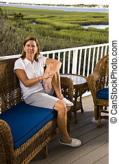 Mid-adult woman sitting alone on terrace