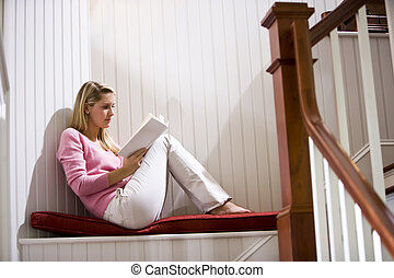 Teenage girl quietly relaxing and reading book by staircase...