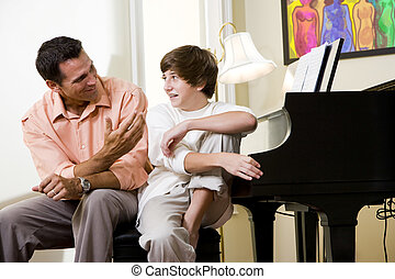 Father with teenage son at home smiling - Father with...