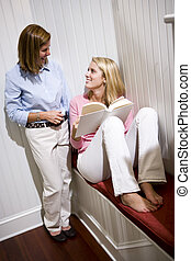 Mother standing beside teenage daughter reading book at home