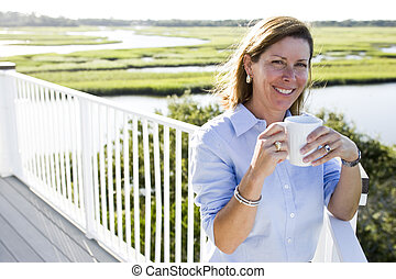 Mid-adult woman having cup of coffee on terrace