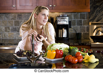 Teenage girl leaning on kitchen counter thinking