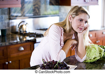 Teen girl leaning on kitchen counter daydreaming