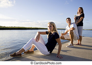 Teenage girl and parents on dock by water relaxing