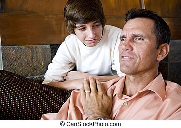 Father with teenage son at home on sofa - Father sitting on...
