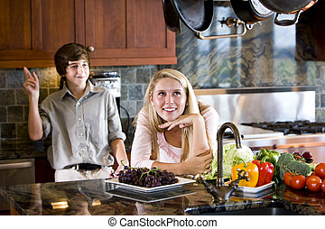 Teenage girl daydreaming in kitchen with brother