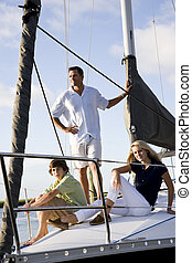 Father and teenage children on sailboat at dock - Father and...