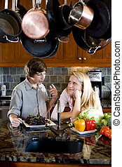 Siblings in kitchen chatting - Teenage sister and brother...