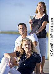 Teenage girl sitting on dock by water with parents - Pretty...
